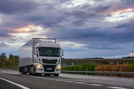 Photo for Refrigerated semi-trailer truck driving on a highway under a dramatic sunset sky. - Royalty Free Image