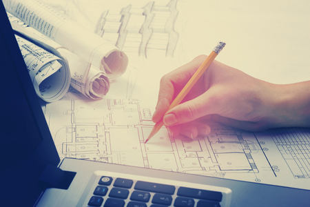 Photo pour Architect working on blueprint. Architects workplace - architectural project, blueprints, ruler, calculator, laptop and divider compass. Construction concept. Engineering tools. Toned image. - image libre de droit