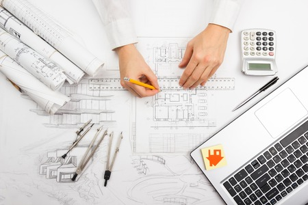 Foto de Architect working on blueprint. Architects workplace - architectural project, blueprints, ruler, calculator, laptop and divider compass. Construction concept. Engineering tools. - Imagen libre de derechos