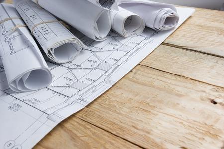 Foto de Architectural project, blueprints, blueprint rolls and divider compass, calipers on vintage wooden background. Construction concept. Engineering tools. Copy space. - Imagen libre de derechos