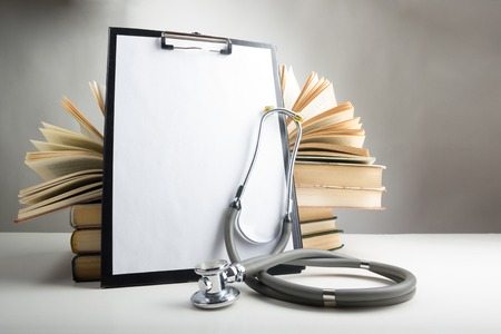 Photo pour Open hardback books on the table, medical clipboard with blank paper or document, report and stethoscope. Medical professional education and information concept. Back to school, copy space. - image libre de droit