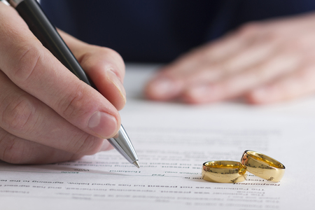 Photo for Hands of wife, husband signing decree of divorce, dissolution, canceling marriage, legal separation documents, filing divorce papers or premarital agreement prepared by lawyer. Wedding ring. - Royalty Free Image