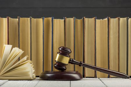 Photo pour Legal Law concept - Open law book with a wooden judges gavel on table in a courtroom or law enforcement office. - image libre de droit