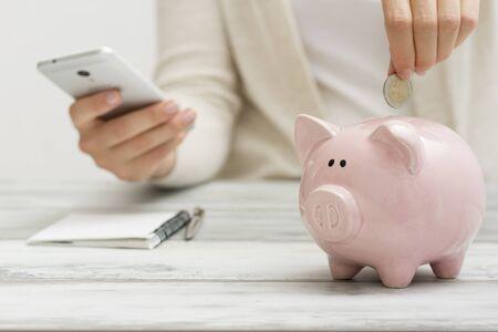 Foto de woman hand putting money coin into piggy for saving money wealth and financial concept - Imagen libre de derechos