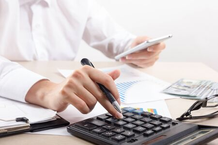 Photo for Close up of female accountant or banker making calculations. Savings, finances and economy concept - Royalty Free Image