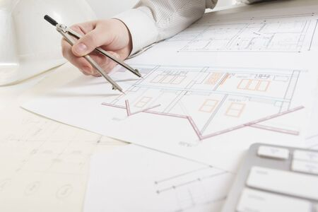 Foto de Architects working on blueprint. Architects workplace - architectural project, blueprints, ruler, calculator, laptop and divider compass. Construction concept. Engineering tools. - Imagen libre de derechos
