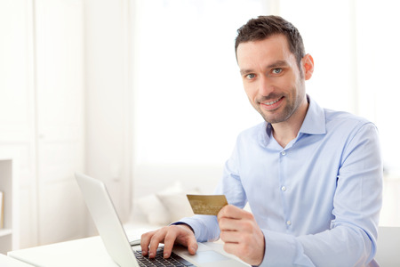 View of a Young business man paying online with credit card