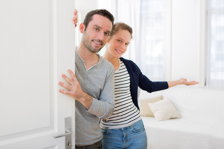 Photo for View of a Young attractive couple welcoming you in his house - Royalty Free Image