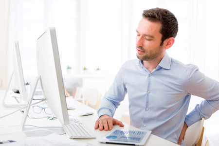 View of a Young attractive man got a back pain at the office