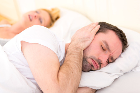 View of a Young man can't sleep because of girlfriend's snoring