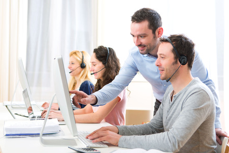 Photo pour View of a Manager training a young attractive people on computer - image libre de droit