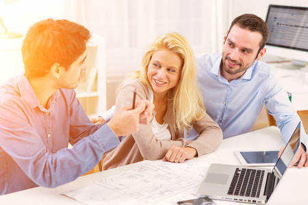 Photo pour View of a young serious couple meeting a real estate agent - image libre de droit