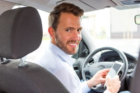 VIew of a Young attractive man using mobile phone in his car