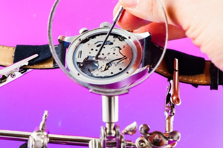 Elegant watch repaired using a magnifier with three handles