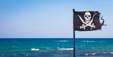 A damaged pirate flag during a strong windy day, with copyspace