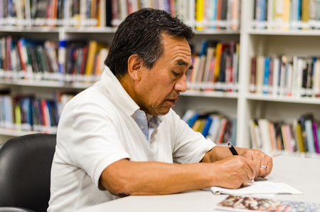 Photo pour Senior man sitting in a library writing in a notepad . - image libre de droit