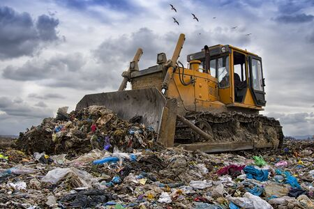 Photo for bulldozer working on landfill with birds in the sky - Royalty Free Image