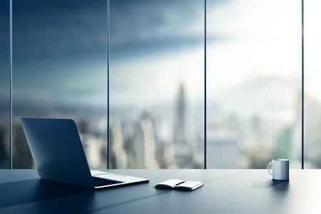 Foto de laptop, cup and diary on table in office - Imagen libre de derechos