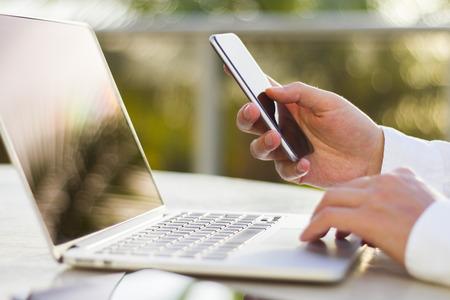 Photo pour businessman with cellphone and laptop at morning - image libre de droit