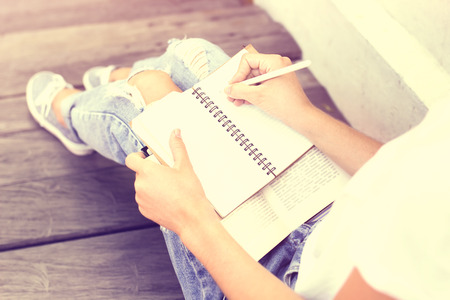 Photo pour Schoolgirl sitting on floor and wrote in a notebook - image libre de droit