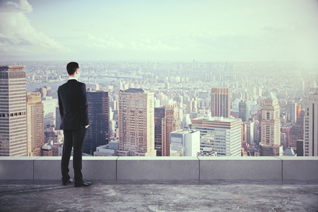 Photo pour Businessman on the roof and looking at the city with skyscrapers - image libre de droit