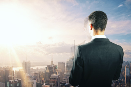 Businessman looking at sunrise from the top of building