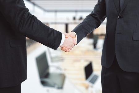 Photo pour Business partners shake hands in the office - image libre de droit