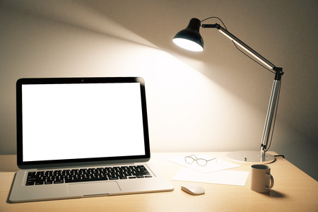Blank white laptop screen with lamp on wooden table, mock up