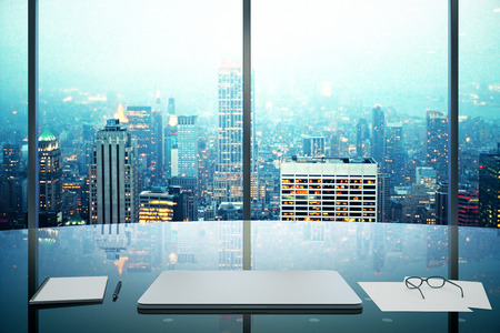 Photo for Modern office with glassy table, laptop and night megapolis city view - Royalty Free Image