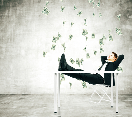 Businessman on a chair in loft room with money falling from the ceiling