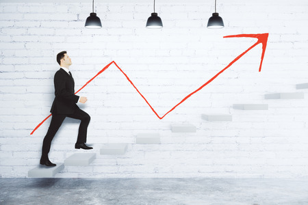 Photo pour Success concept with businessman climbing the stairs and red arrow on white brick wall - image libre de droit