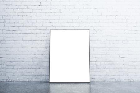 Foto de Blank white picture frame on concrete floor in empty room with white brick wall, mock up - Imagen libre de derechos