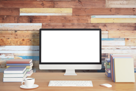 Photo pour Blank computer screen with keyboard, piles of books and cup of coffee on wooden table and wooden wall, mock up - image libre de droit