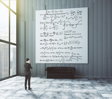 Big white poster with equations, leather sofa and businessman in loft room with big windows