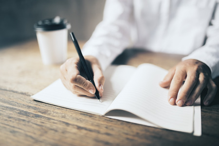 Man writing in blank diary and paper coffee cup on wooden table
