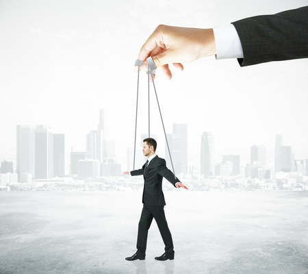 Hand manipulating businessman puppet on ropes. Abstract city background. Concept of control