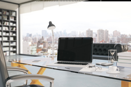 Foto de Closeup of creative office workplace with blank laptop, coffee cup, smartphone, hourglass and other items with bookshelf and window with city view in the background. Mock up, 3D Rendering - Imagen libre de derechos
