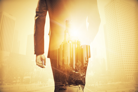 Photo pour Back view of businessman in suit walking on abstract city background with sunlight. Double exposure - image libre de droit