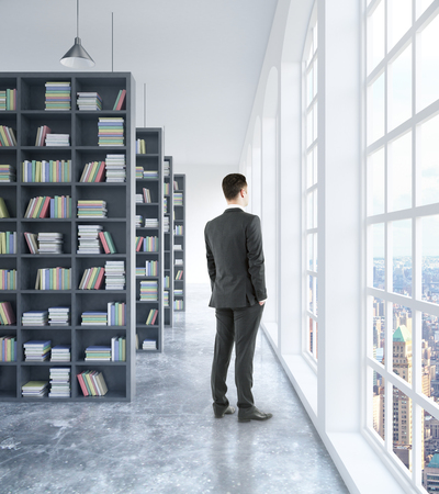 Businessman looking out of window in modern concrete library interior with book shelves, daylight and city view. 3D Rendering