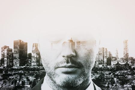 Photo pour Portrait of thoughtful young businessman on abstract city background. Research concept. Double exposure - image libre de droit