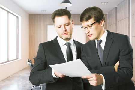 Handsome caucasian businessmen discussing contract together in modern office