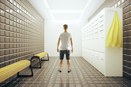Back view of young man standing in bright gym changing room interior. 3D Rendering