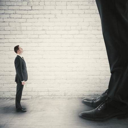 Photo pour Side view of tiny businessman looking up to huge one. Small and big businesses concept - image libre de droit