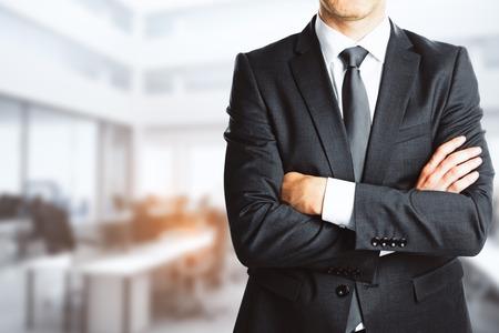 Foto de Businessman with folded arms on blurry interior background. Confidence concept. 3D Rendering - Imagen libre de derechos