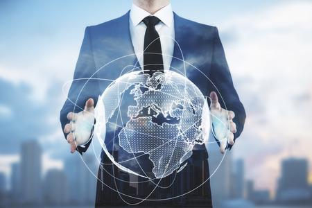 Photo pour Businessman holding abstract digital globe on blurry city background. Communication concept. Double exposure - image libre de droit