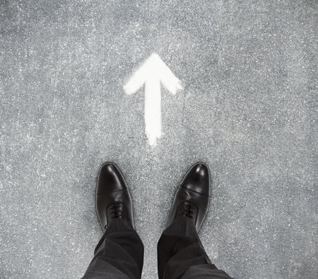 Photo pour Top view of businessmen feet on concrete floor with drawn arrow. Improvement concept  - image libre de droit