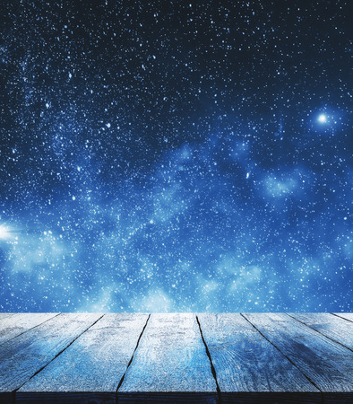 Blank wooden surface on starry sky background. Dreams and design concept