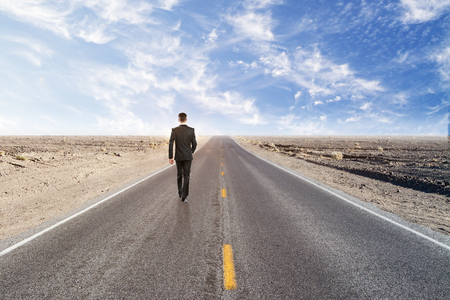 finding way concept with businessman walking on empty road in desert with blue sky. 3D render