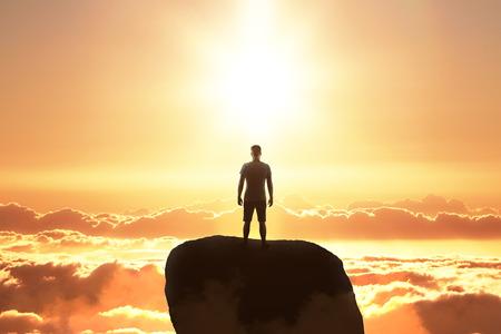 Foto de Backlit businessman on rock looking into the distance on sky background. Research and future concept - Imagen libre de derechos