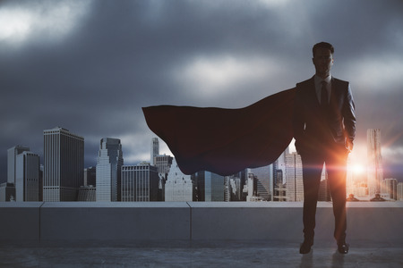 Photo pour Businessman with red hero cape standing on rooftop with city background. Leadership and success concept - image libre de droit